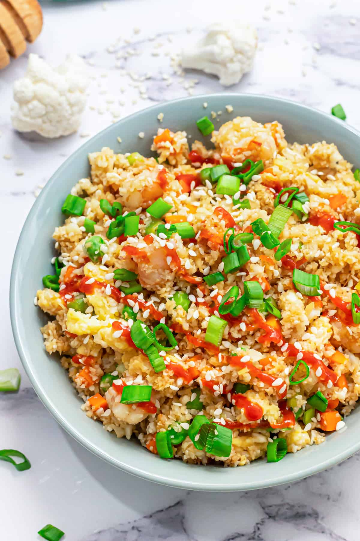 A bowl filled with healthy cauliflower fried rice topped with sriracha and sesame seeds.