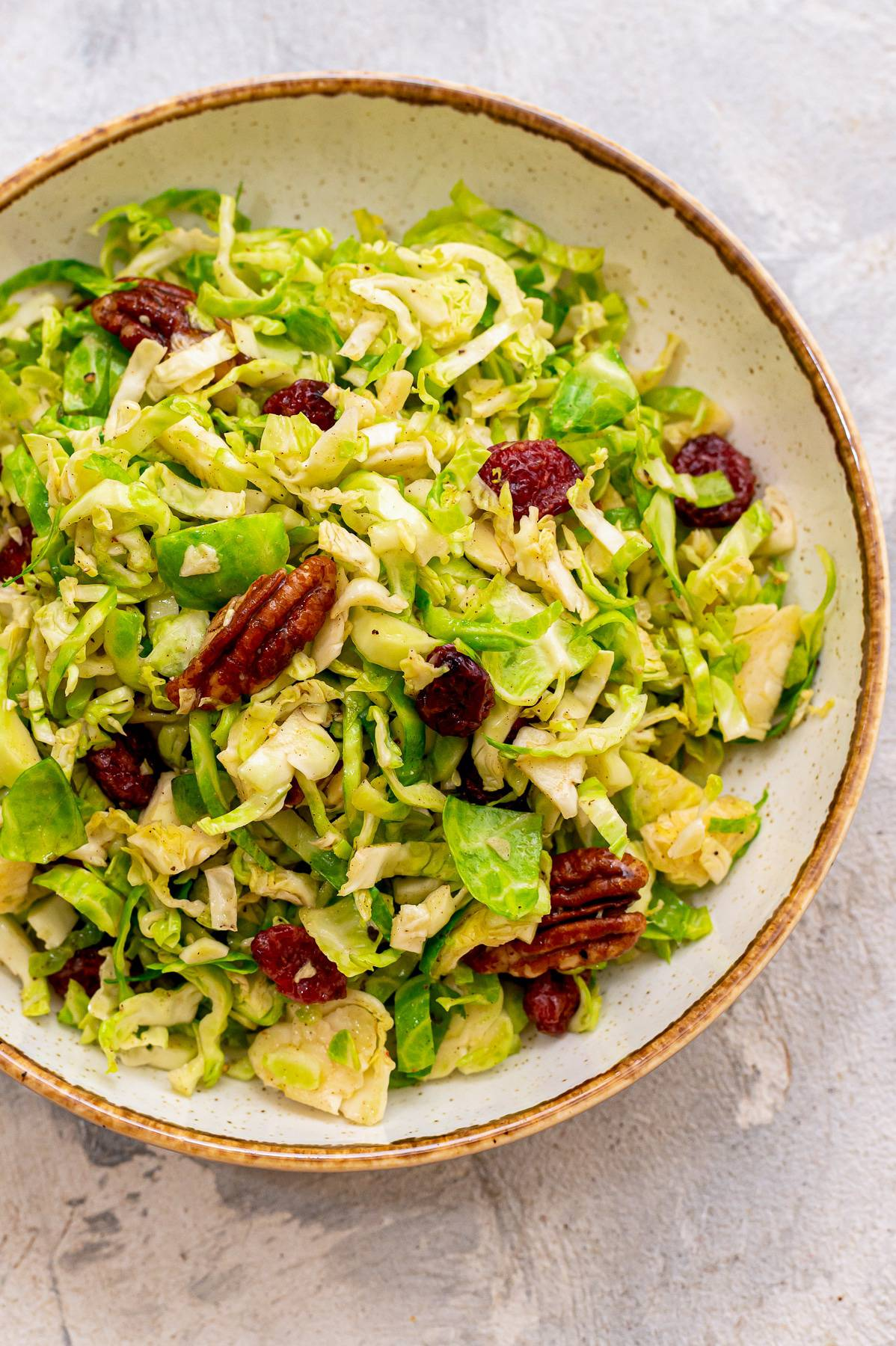 Brussels sprout slaw in a bowl with cranberries and pecans.