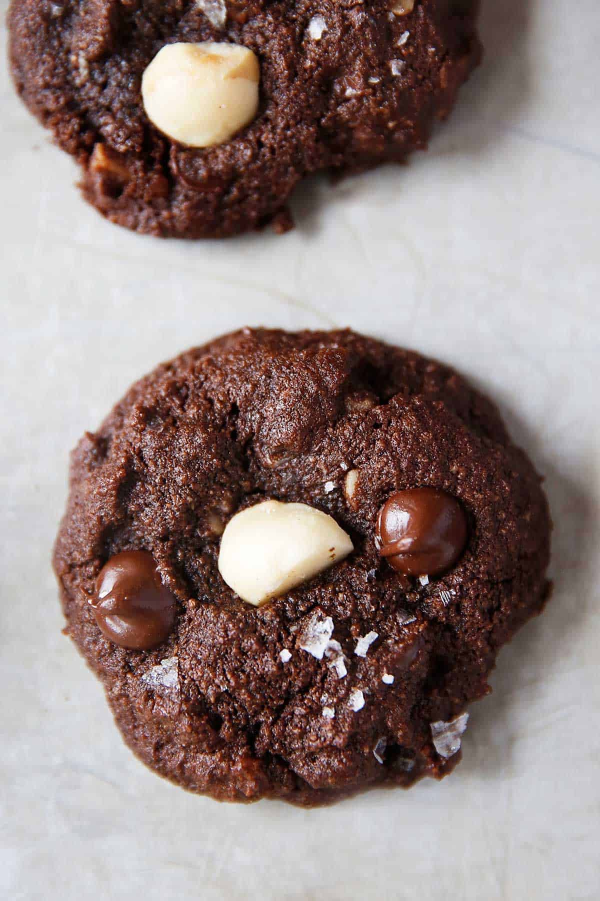 A double chocolate macadamia nut cookie with sea salt on top on a baking sheet.