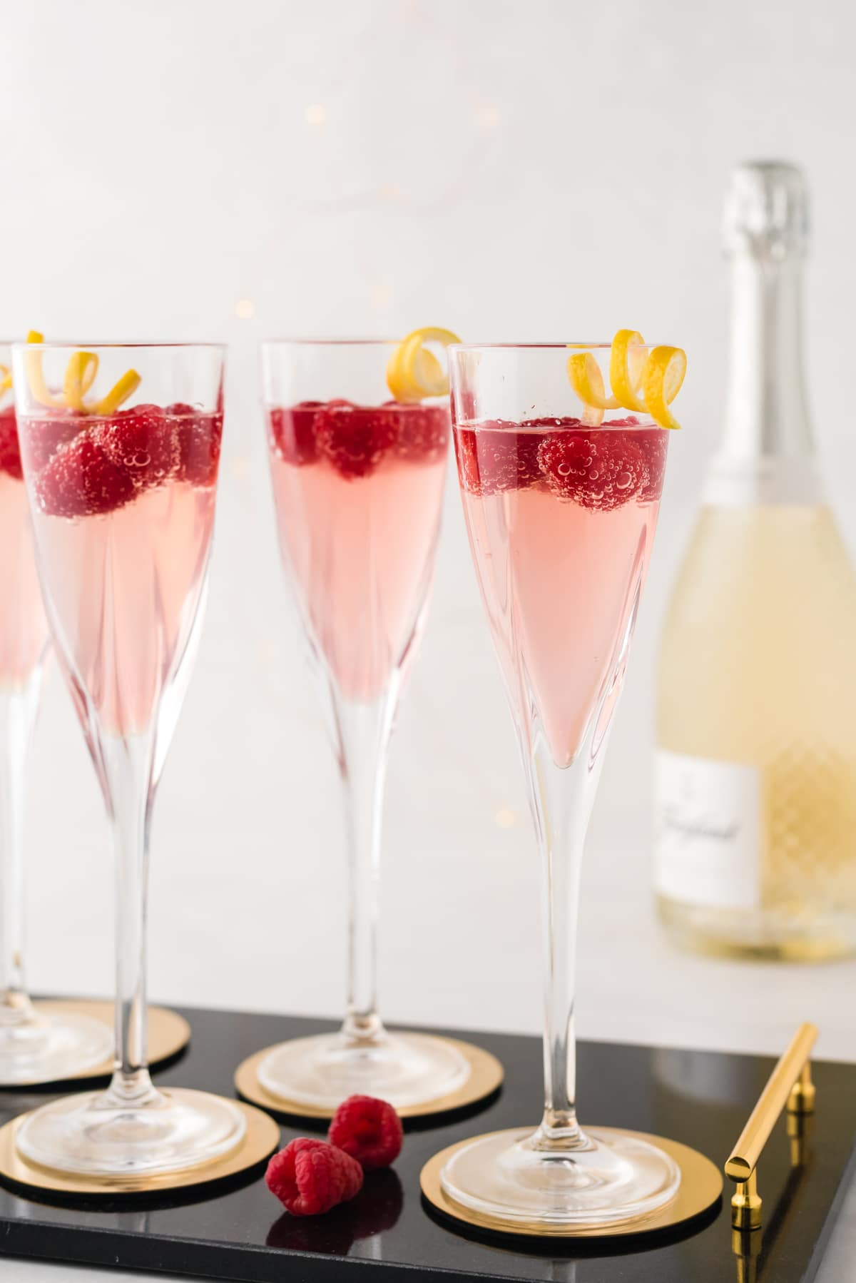 Champagne glasses with raspberries and a lemon twist.