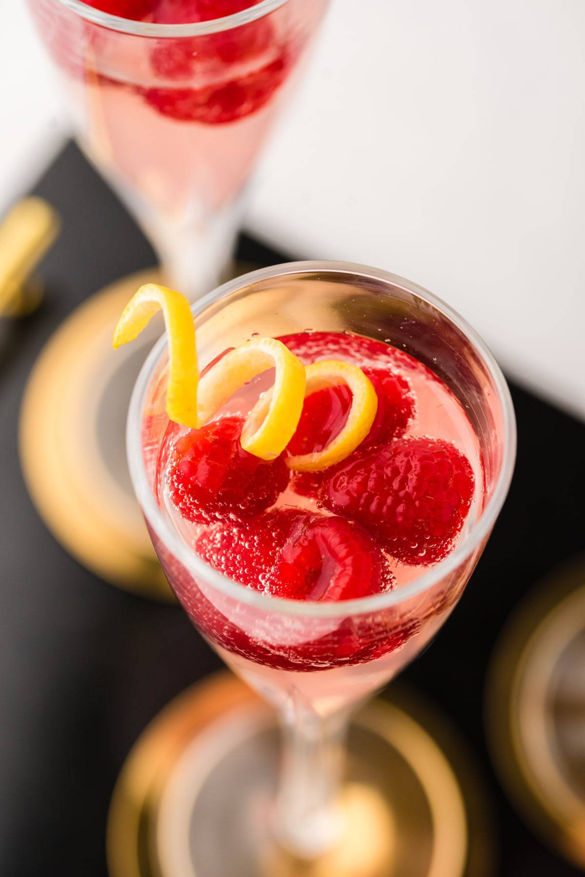 French kiss cocktail with raspberries and a lemon twist.