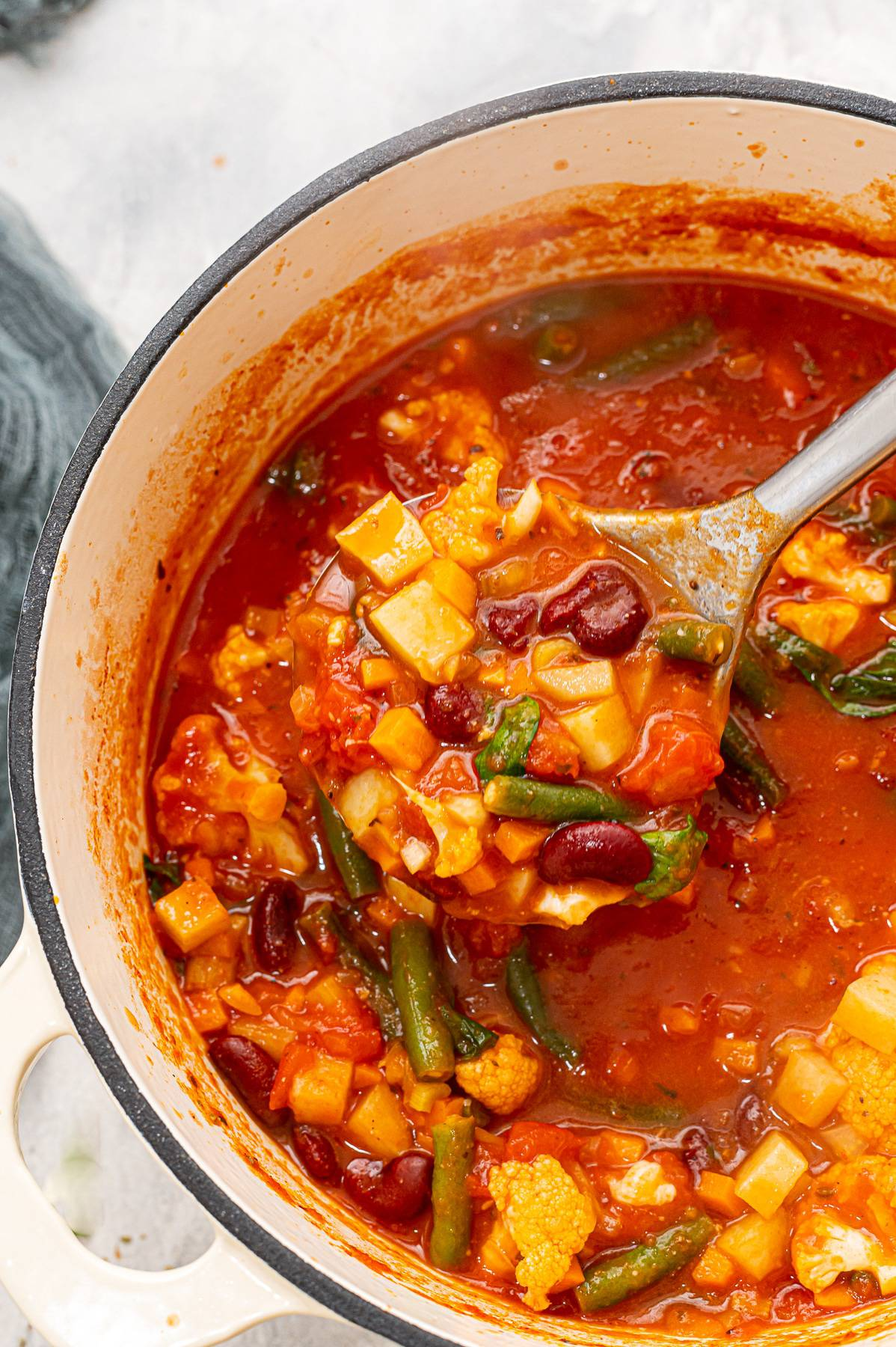 Rustic Tomato Soup with Veggies in a pot with a spoon in it.