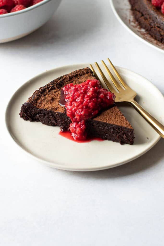 A slice of Paleo Flourless Chocolate cake with a quick raspberry sauce.
