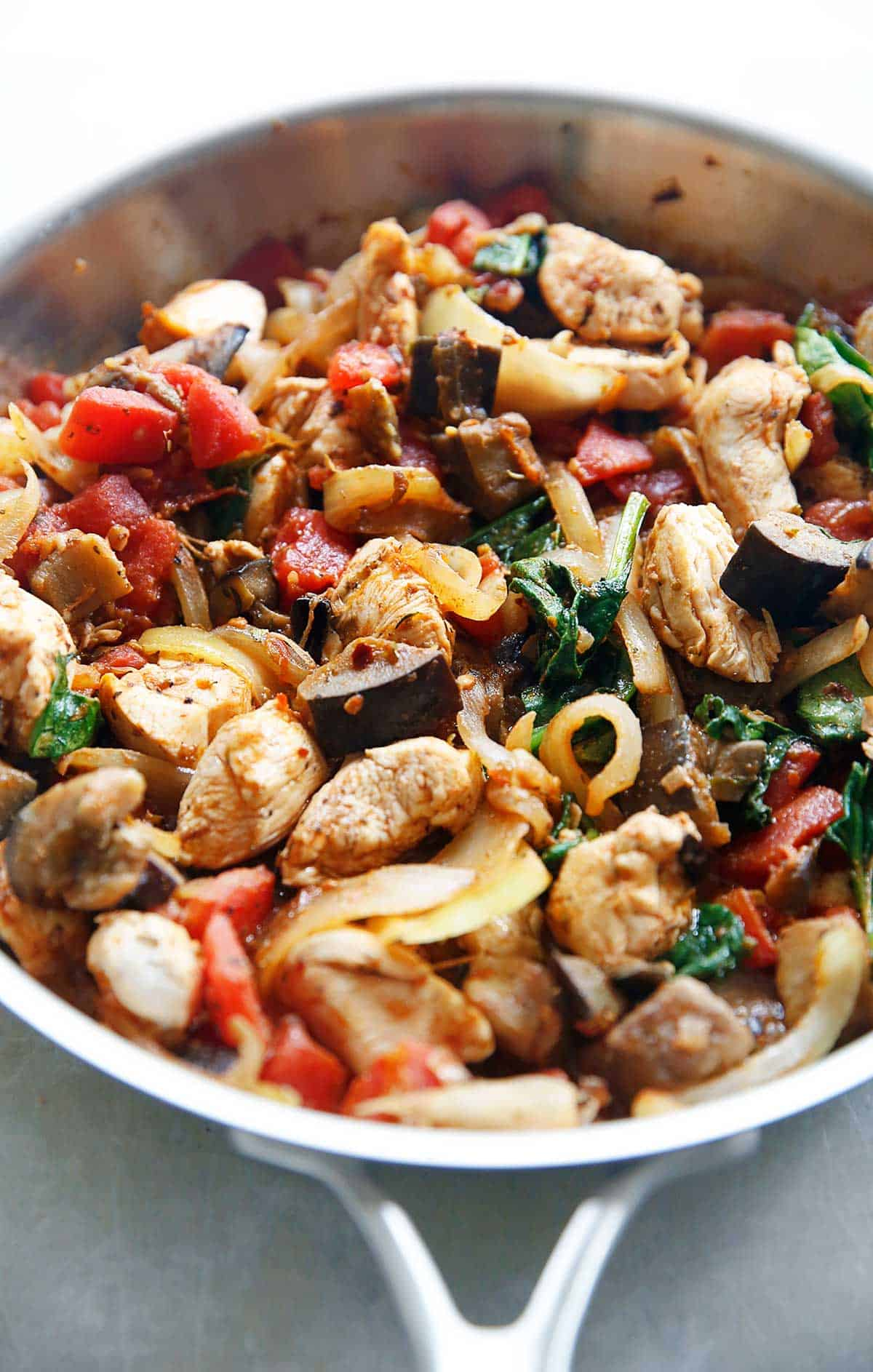 Chicken and eggplant with tomatoes and other veggies in a pan