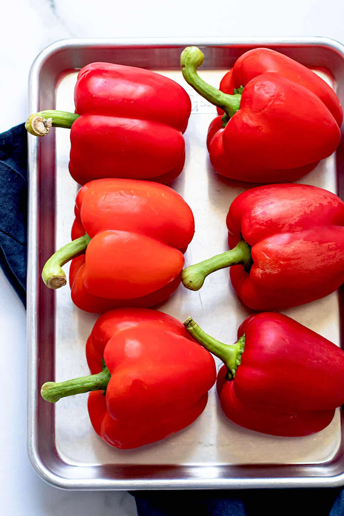 Red peppers on a baking sheet.
