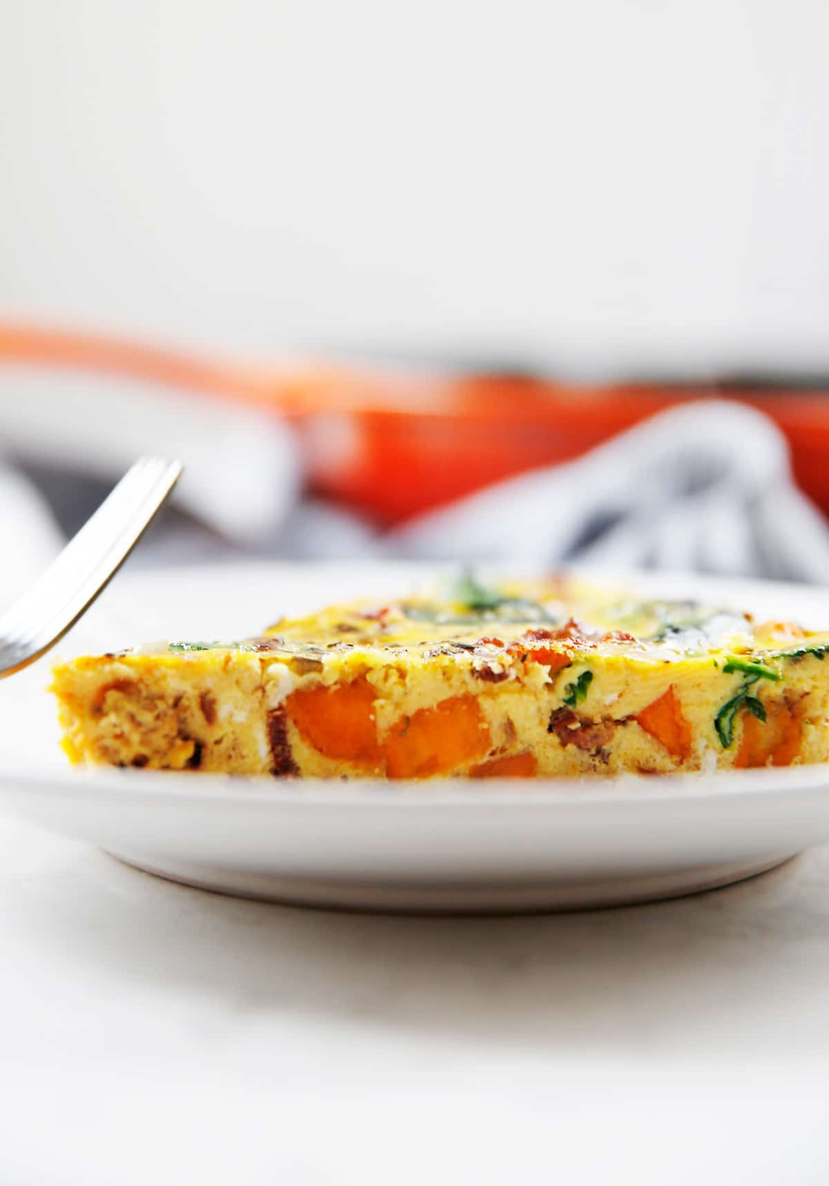 A slice of frittata with sweet potatoes on a plate.