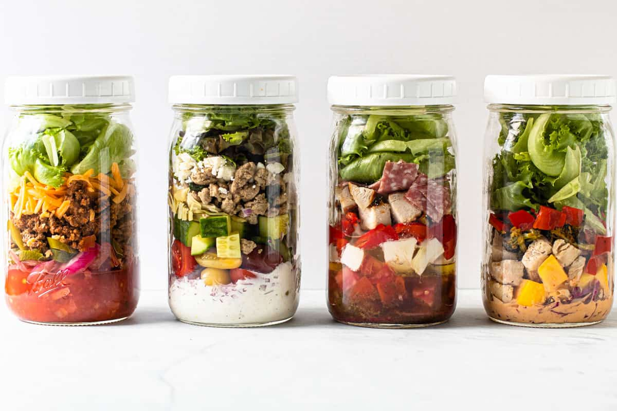 Four different salads in a jar with lids on them.