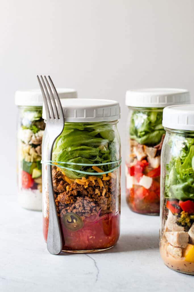 Mason jar salads with a fork attached to it.