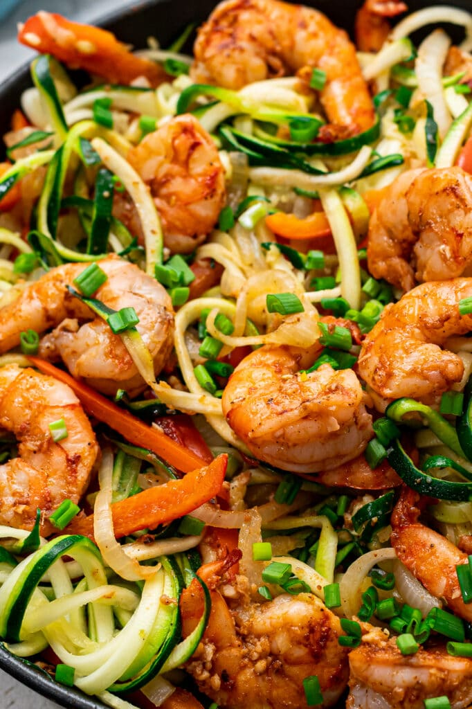 A close up view of shrimp and noodles with veggies.
