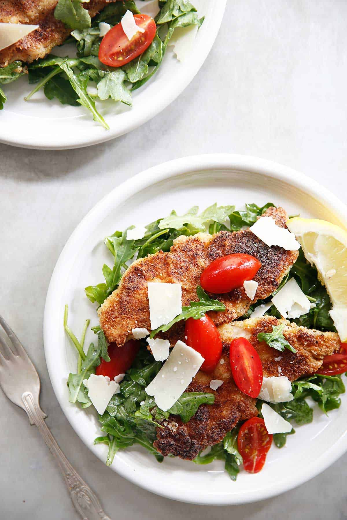 Paleo breaded chicken with salad on plates