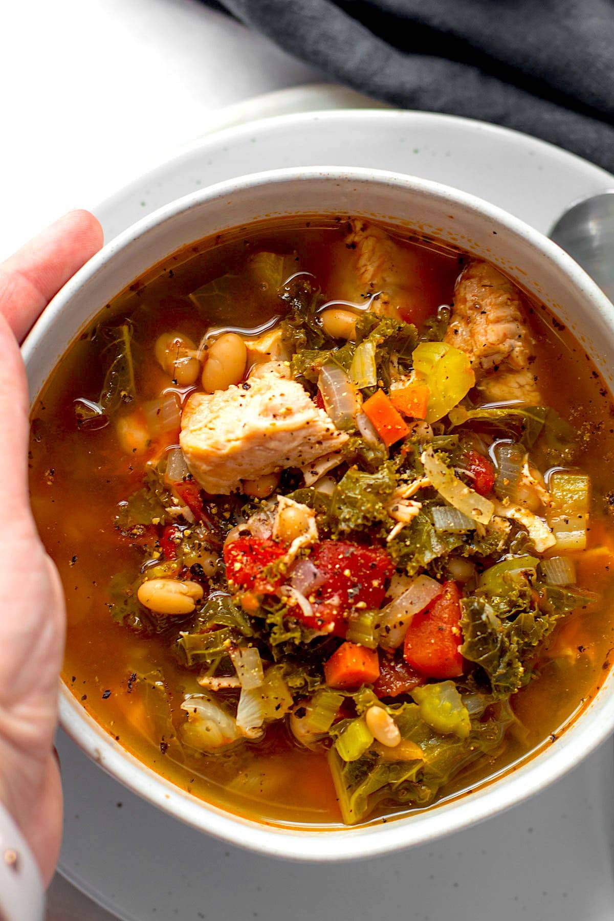 A bowl of turkey kale soup with tomatoes in a bowl.