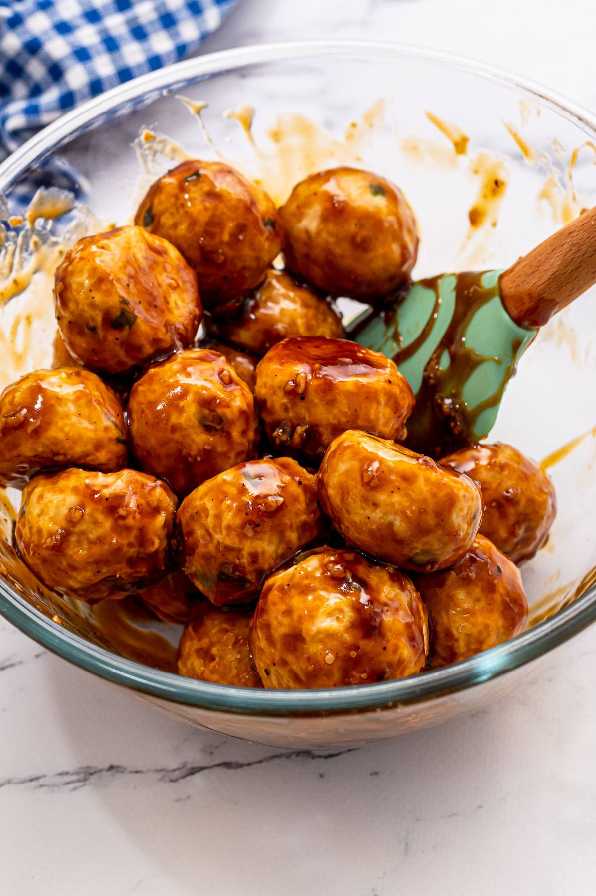 Asian meatballs being tossed in sweet sauce.