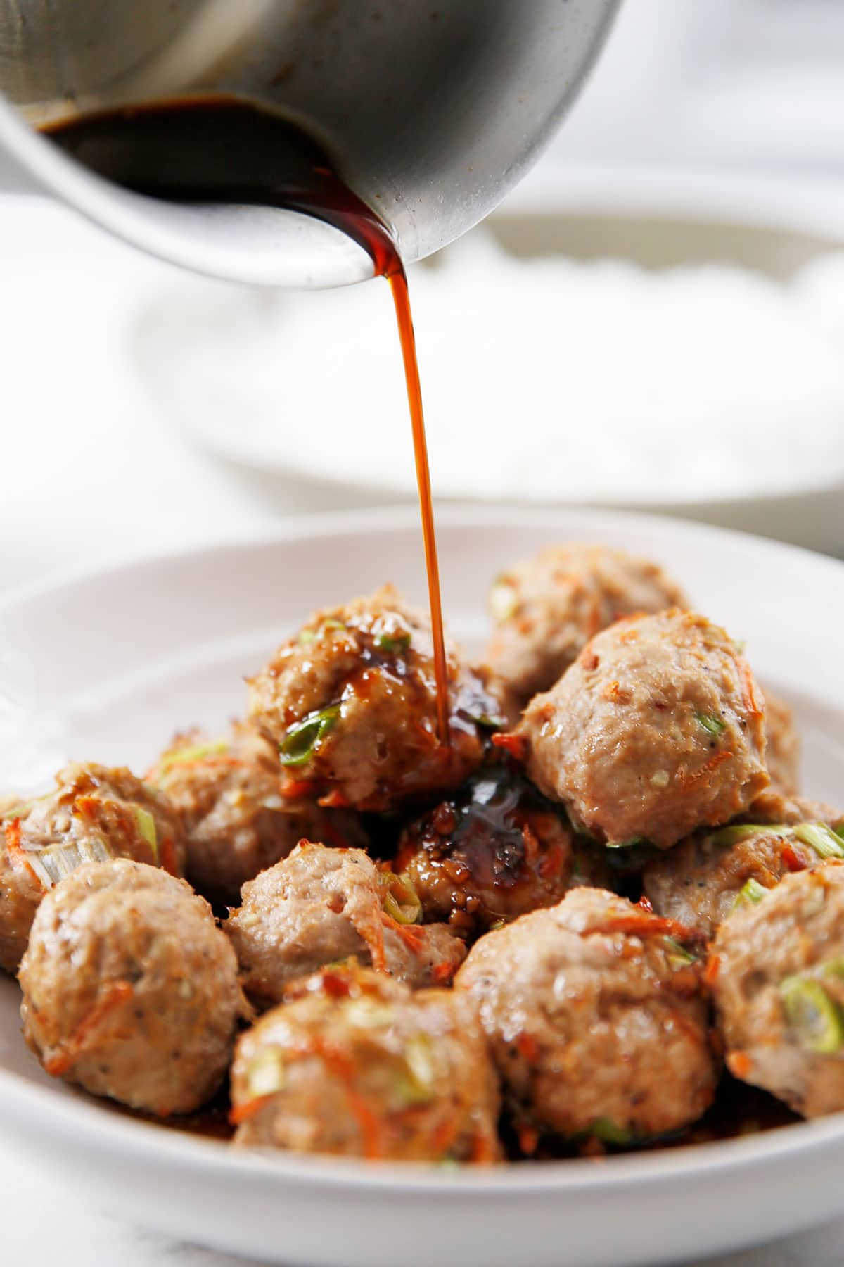 Pouring sauce over thai meatballs.