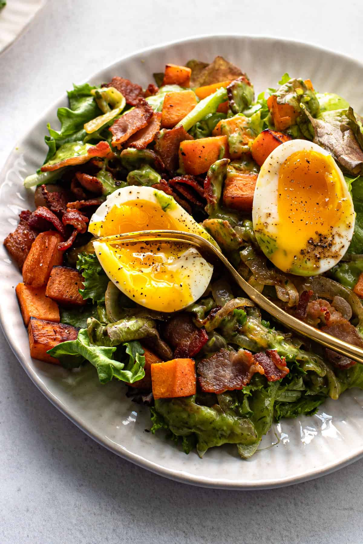 Breakfast salad on a plate topped with a soft-boiled egg.