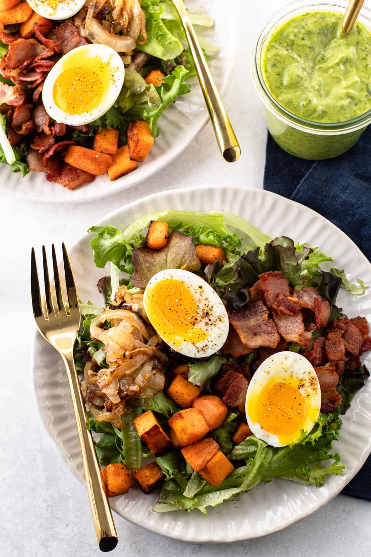 Breakfast salad with soft-boiled eggs, bacon, potatoes and onions.