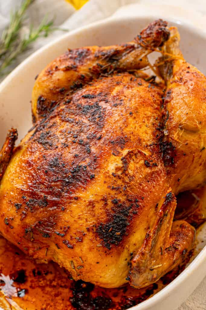 A whole chicken cooked in the slow cooker on a platter.