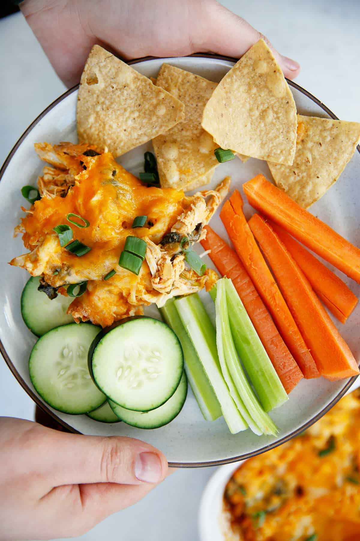A plate of buffalo chicken dip with chips and veggies.