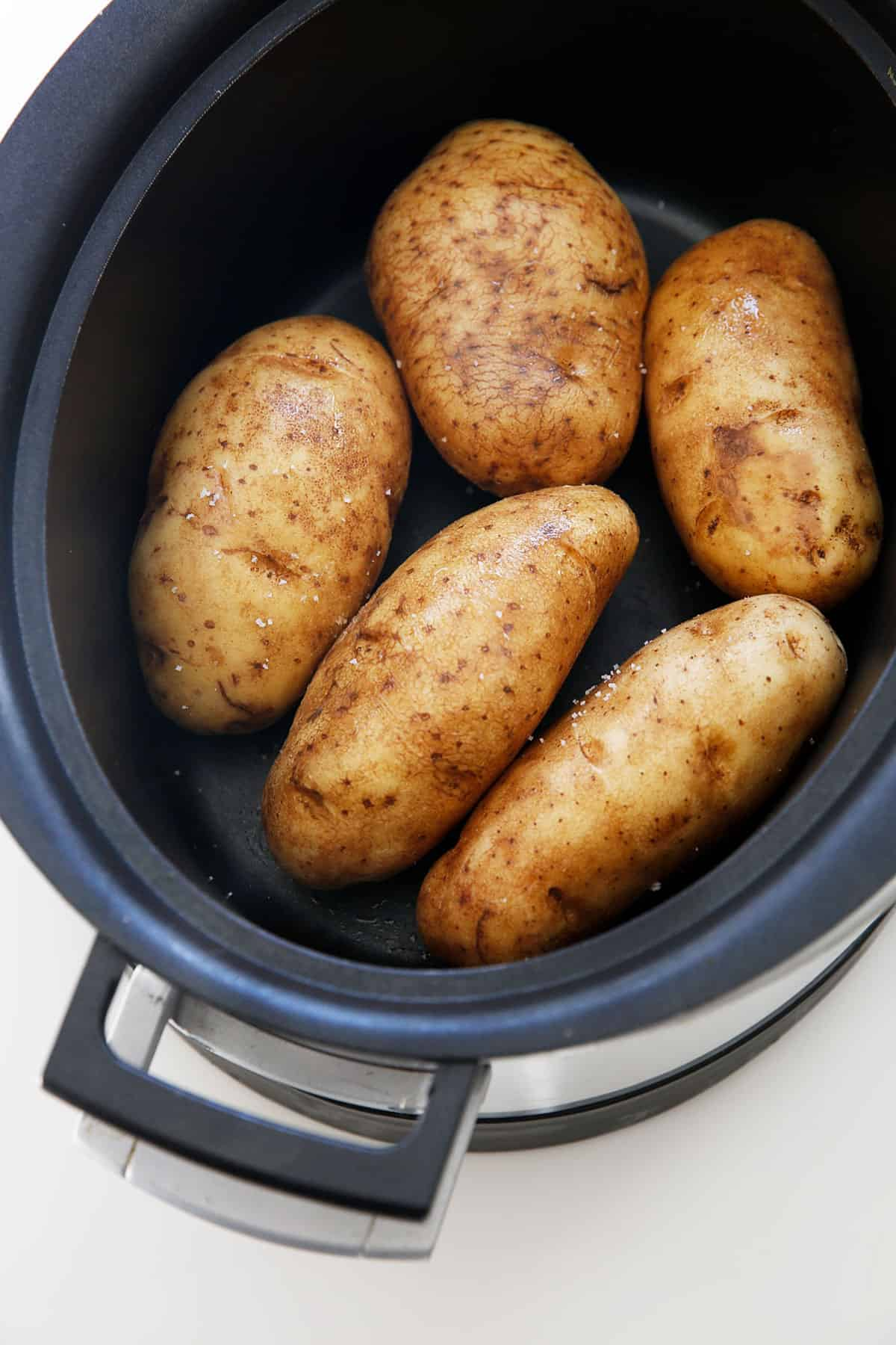 baked potatoes in the slow cooker ready to cook