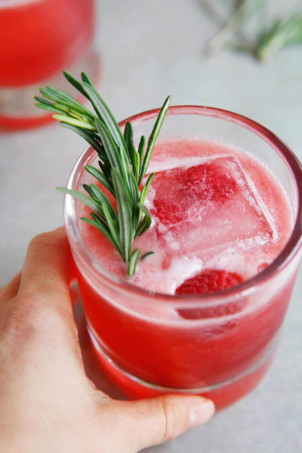 A hand holding a pink raspberry cocktail made from gin and raspberries.