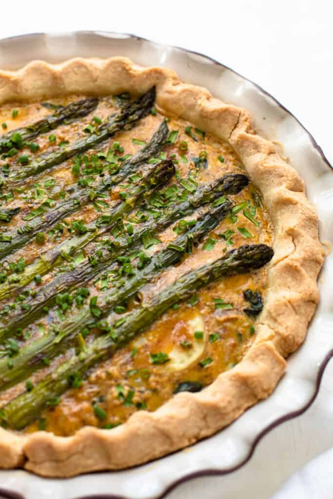 A spring vegetable quiche layered with whole asparagus spears.