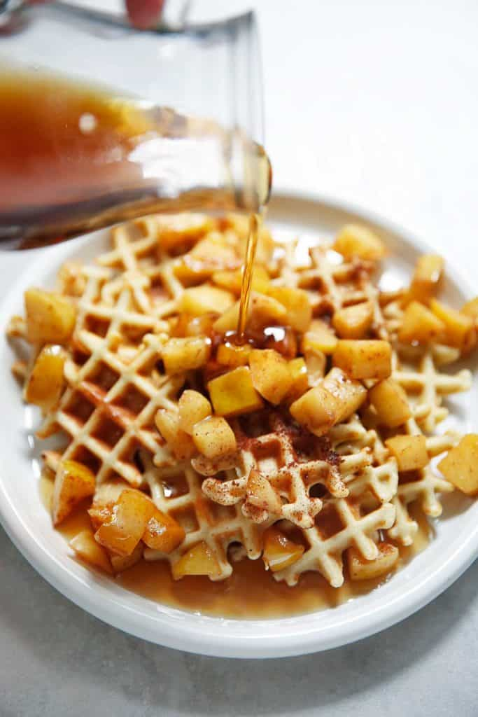 Mini waffles on a plate with apples and maple syrup.