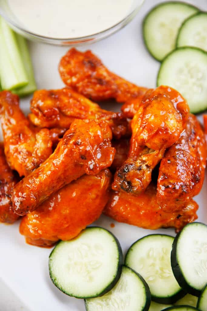 Saucy baked buffalo wings on a platter next to veggies and dip.