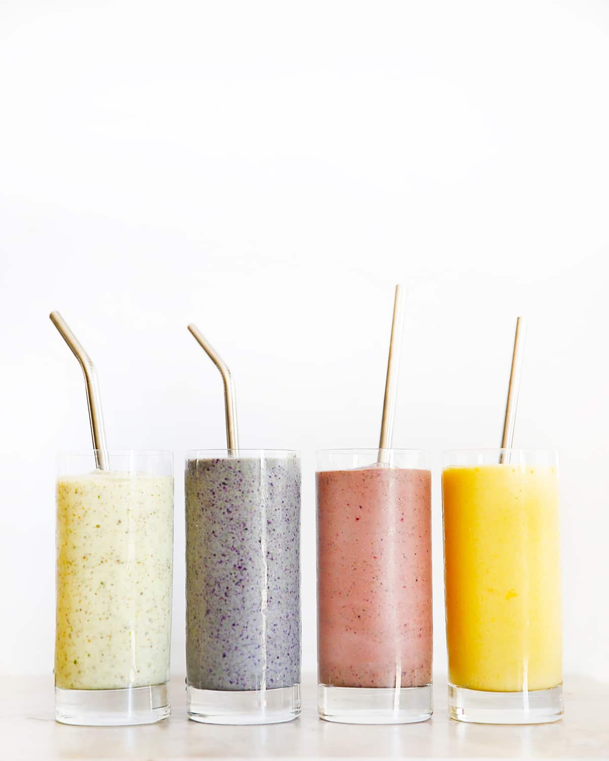 Four colorful smoothies with straws .