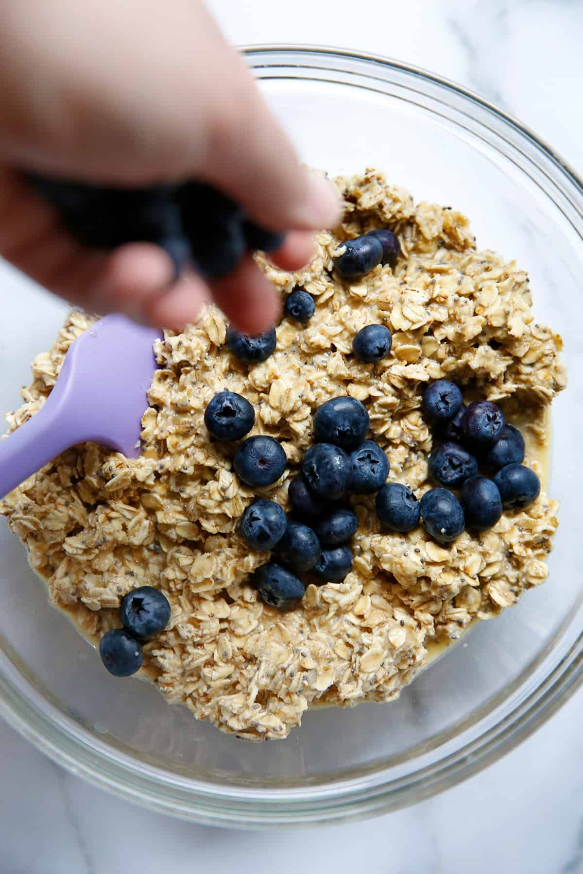 Putting blueberries inside of the bowl with oats