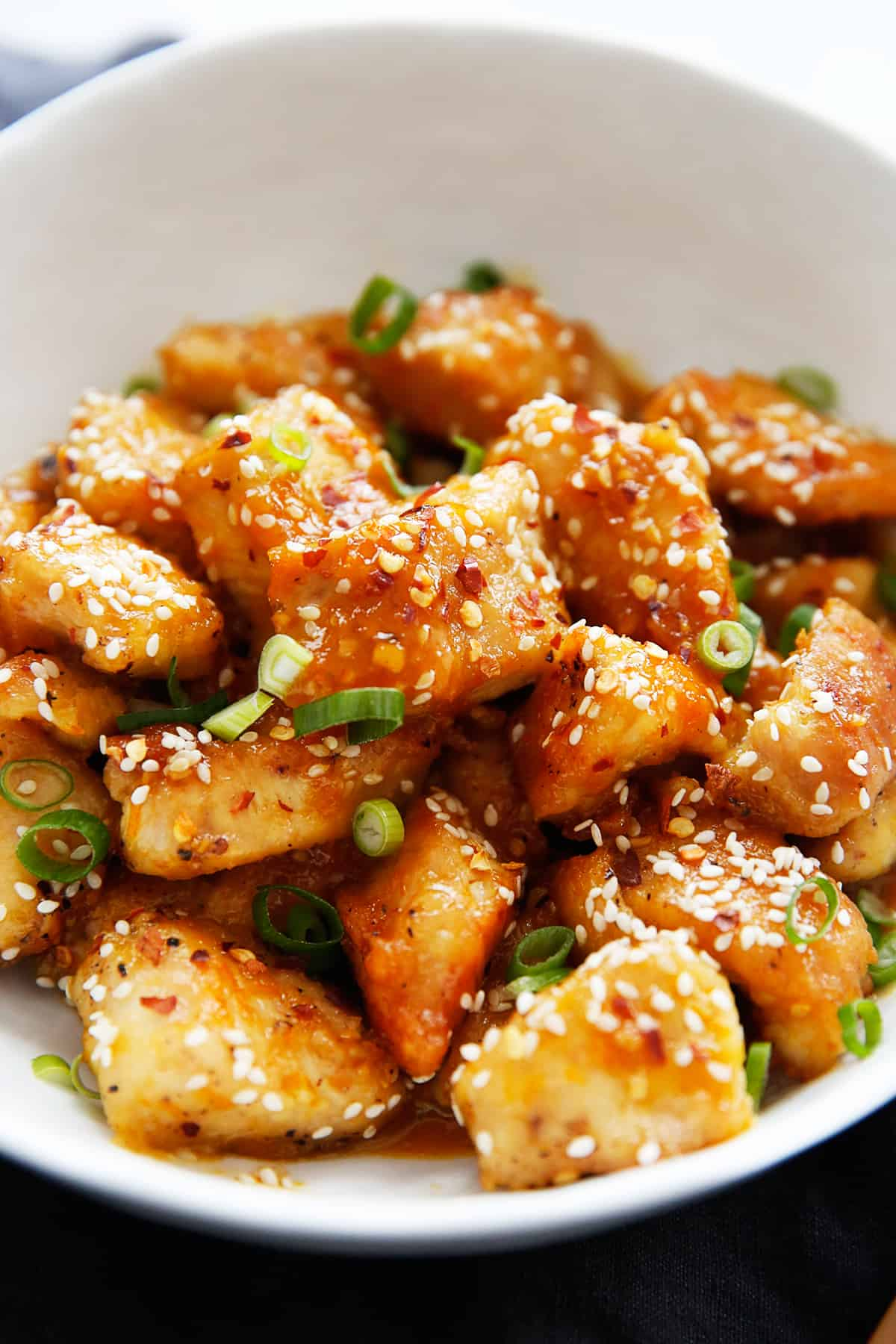 Healthy orange chicken in a bowl with garnish