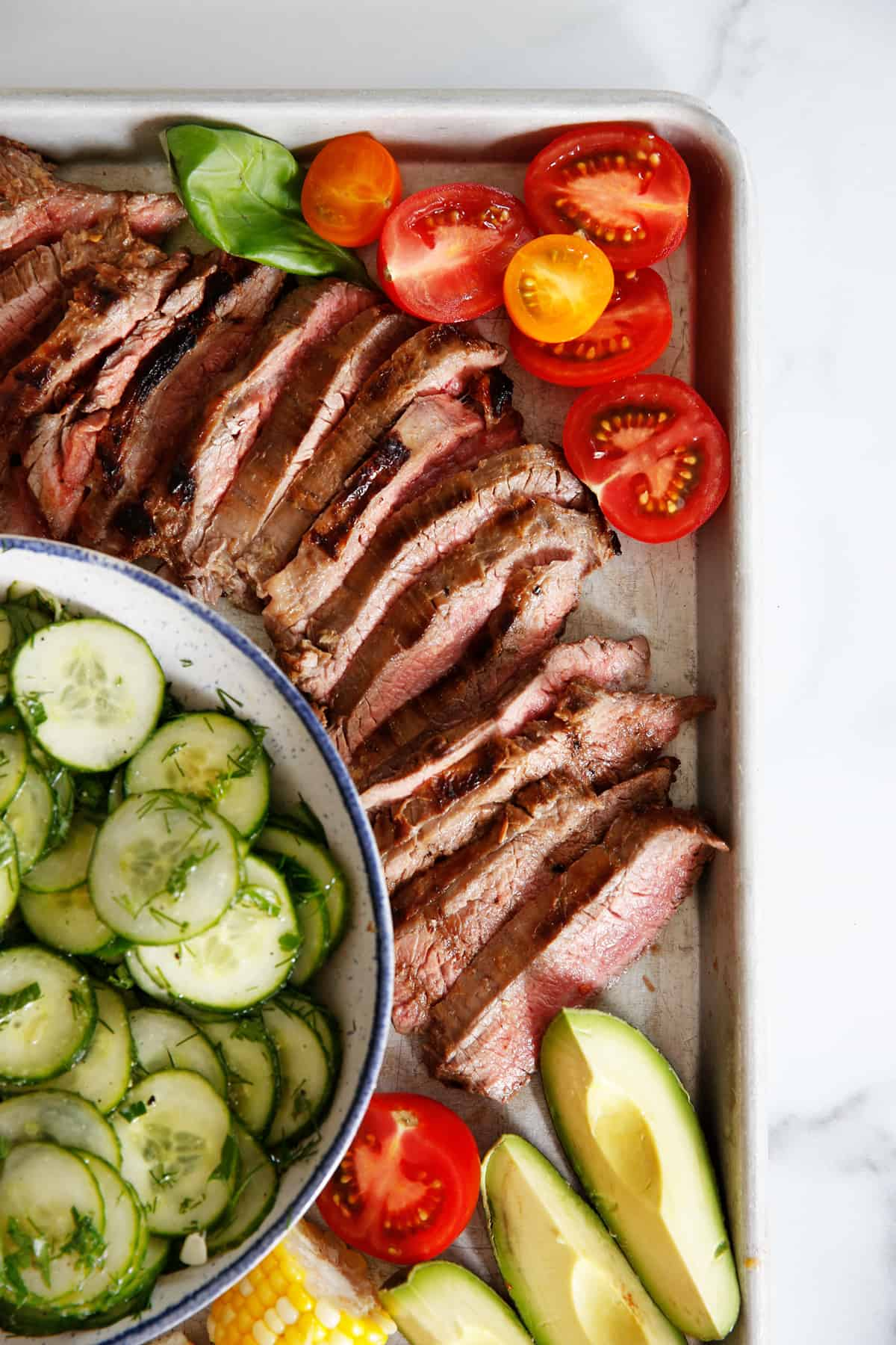 A platter of flank steak surrounded by salads and tomatoes.