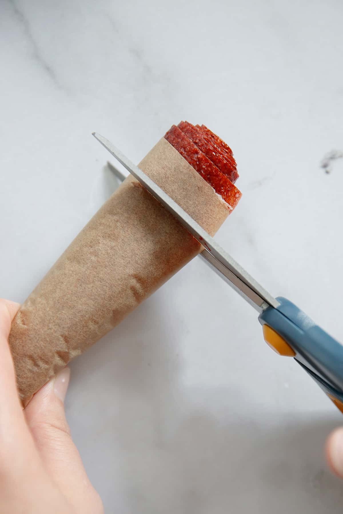Cutting strawberry leather into strips with scissors