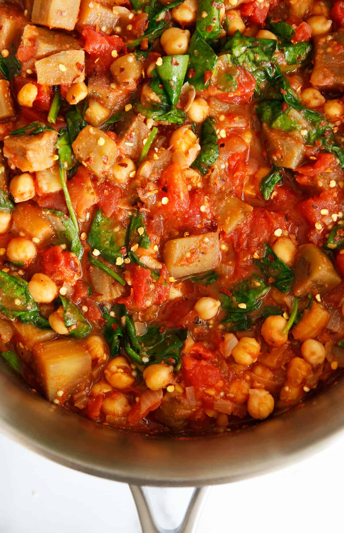 Tomato and eggplant chickpea stew in pot with spinach