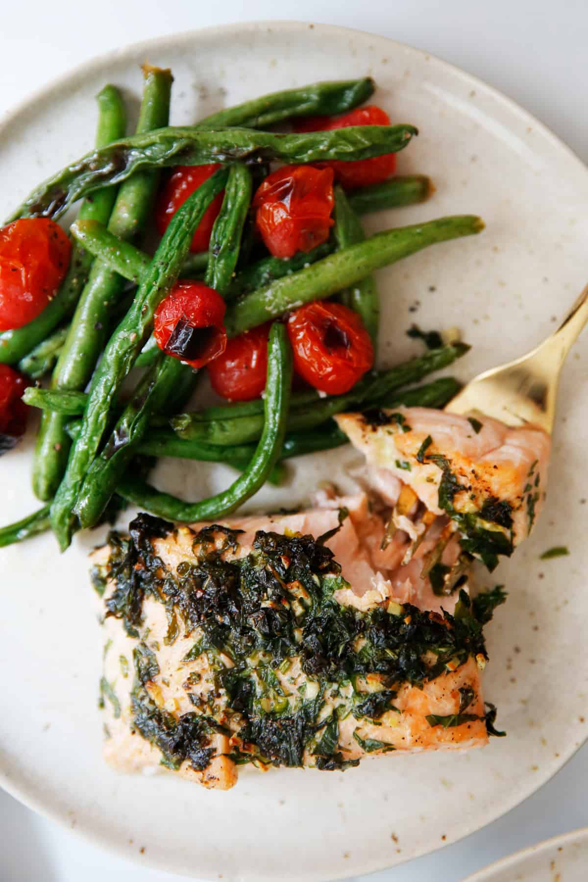 herb butter salmon with tomatoes on a plate