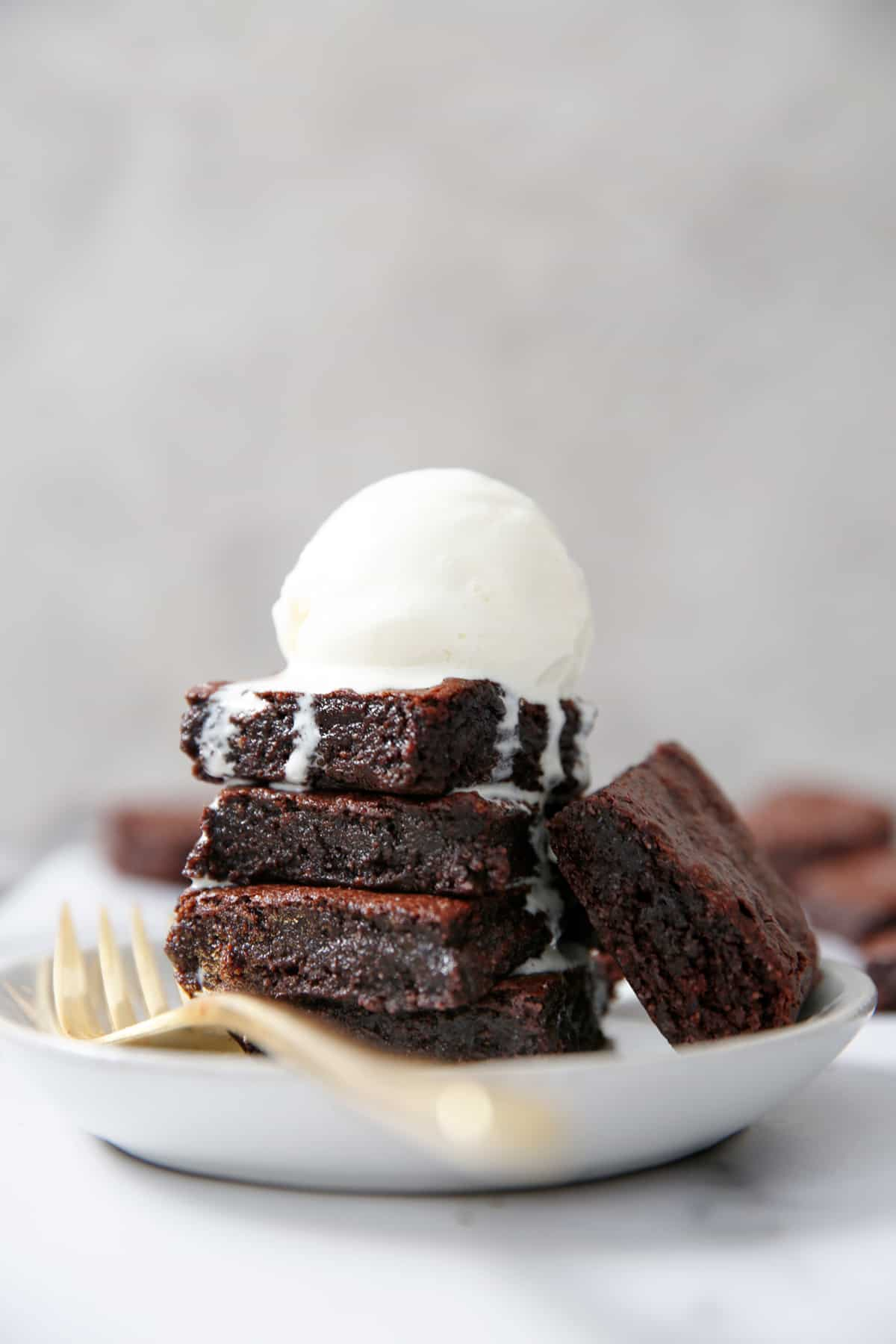 Gluten free and dairy free brownies stacked up with dripping ice cream on them