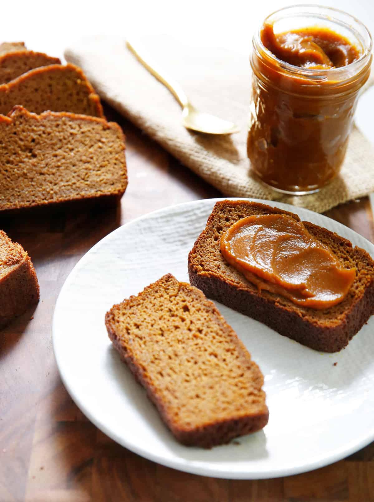 slice of paleo pumpkin bread with pumpkin butter on a plate