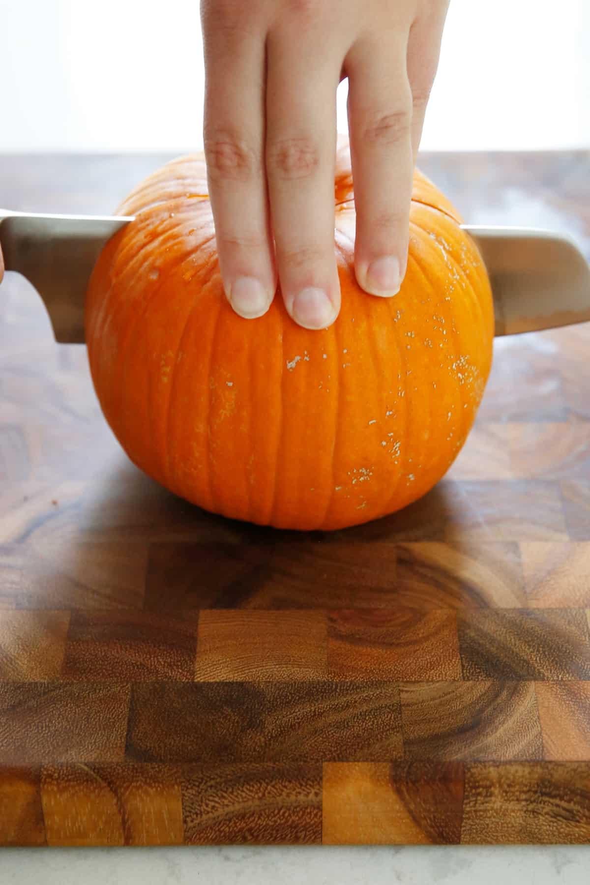 cutting through a fresh pumpkin
