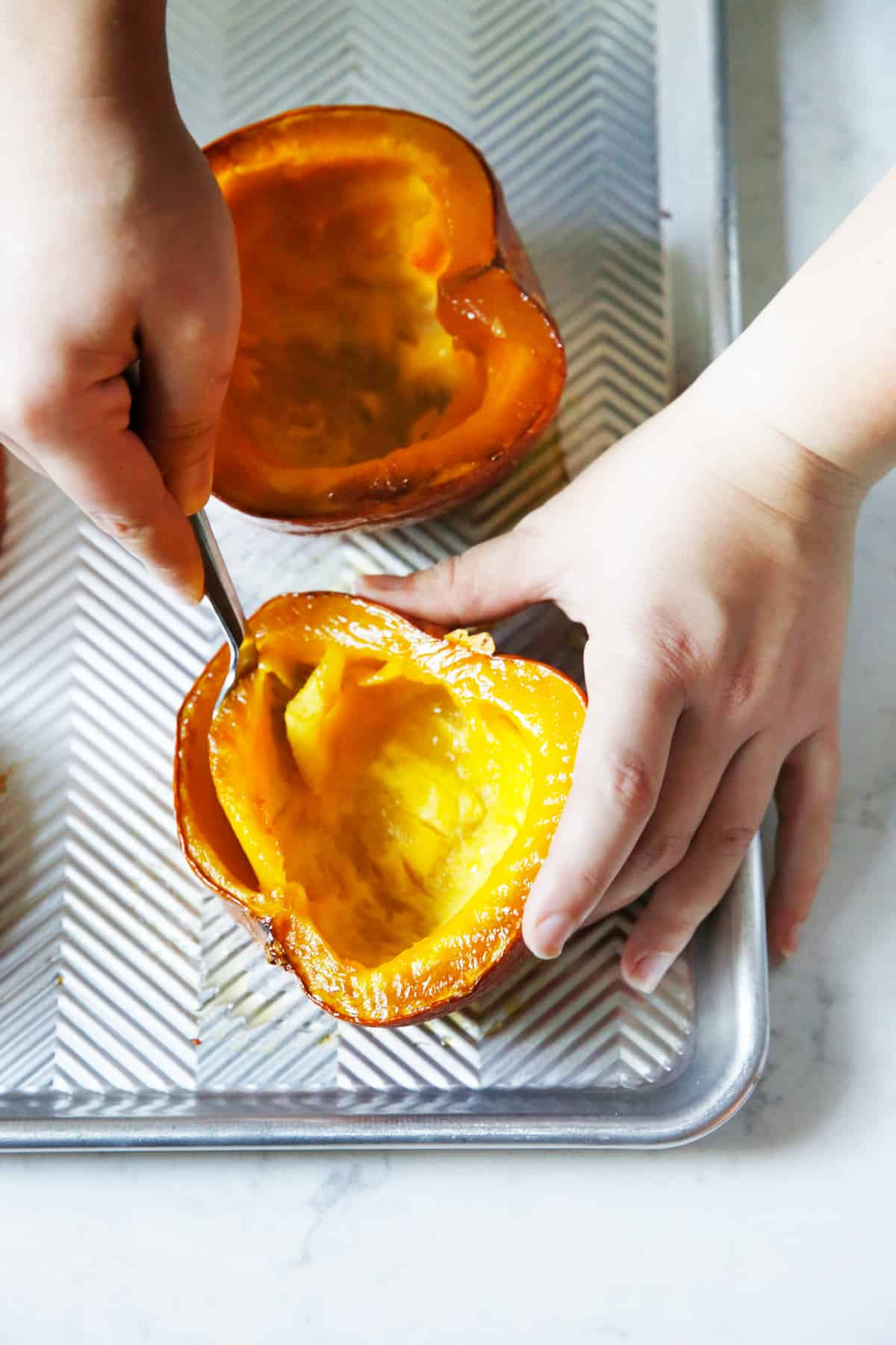 scooping out roasted pumpkin with a spoon