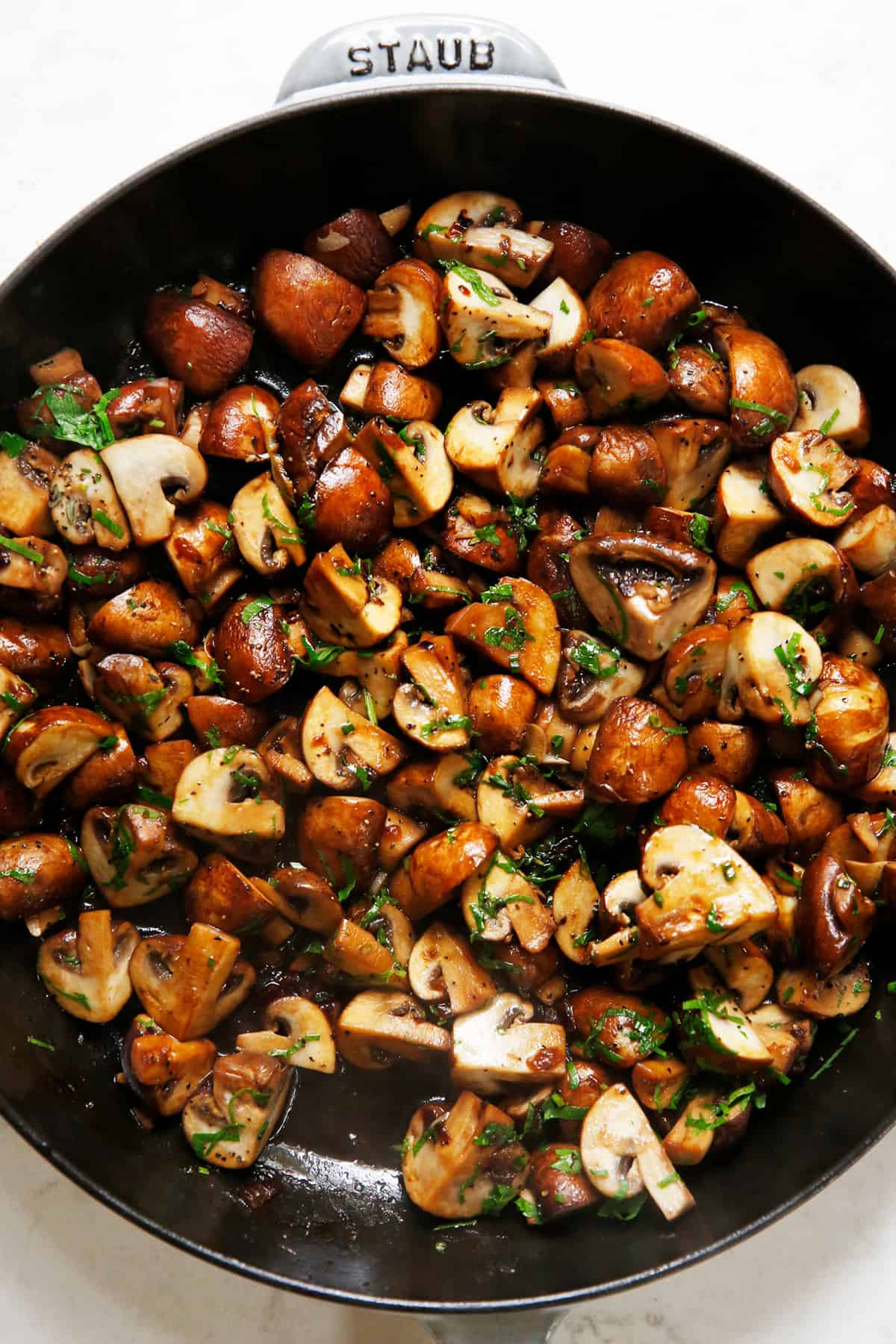 Garlic mushrooms with tons of herbs in a saute pan