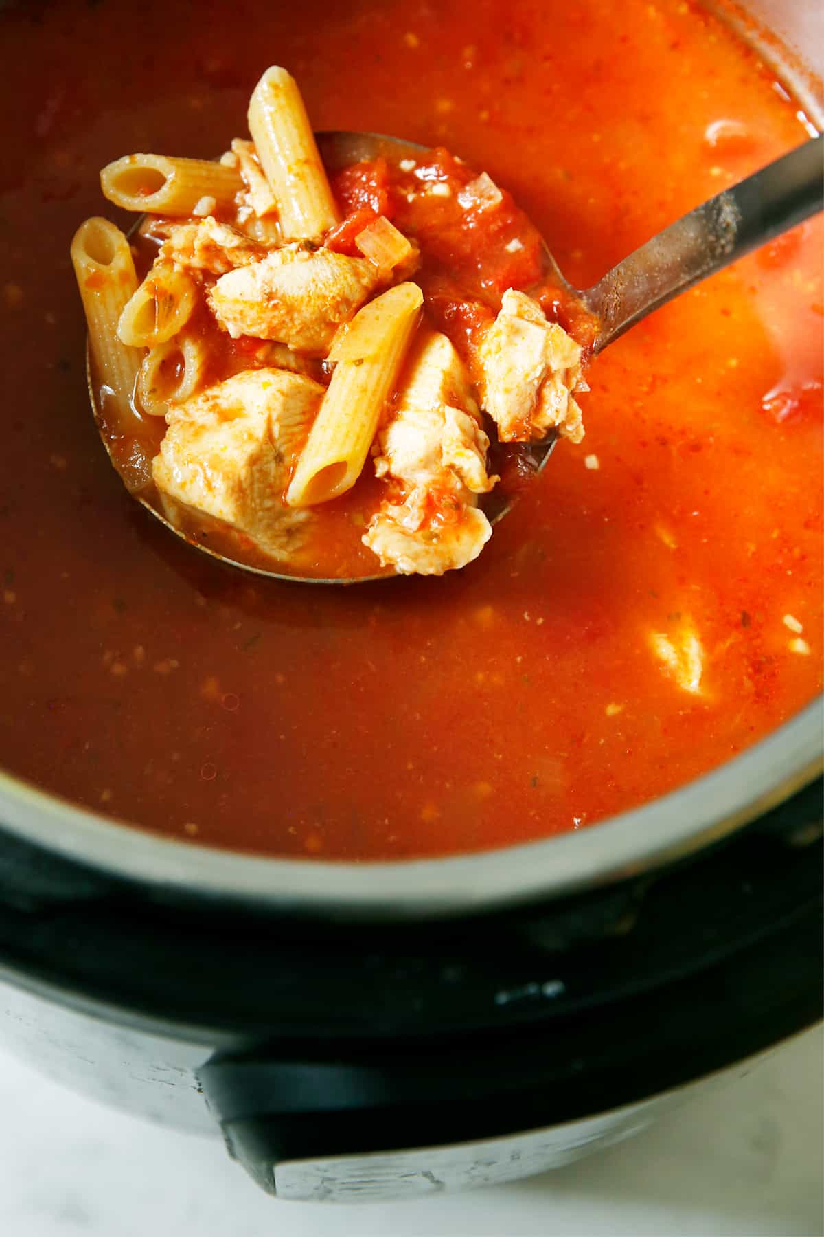 Instant pot chicken parm soup with a ladle