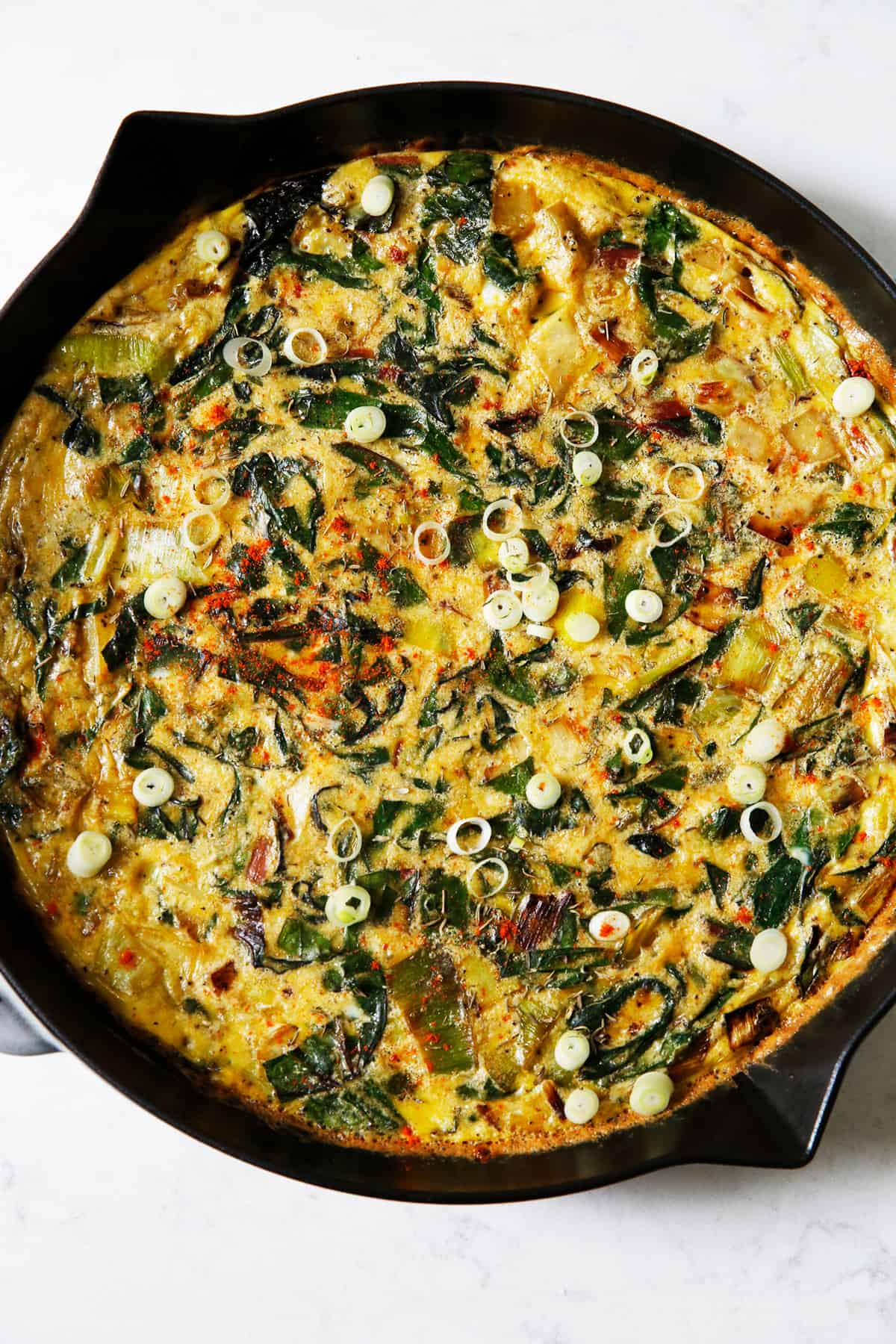 A frittata in a cast iron skillet with potatoes and leeks.