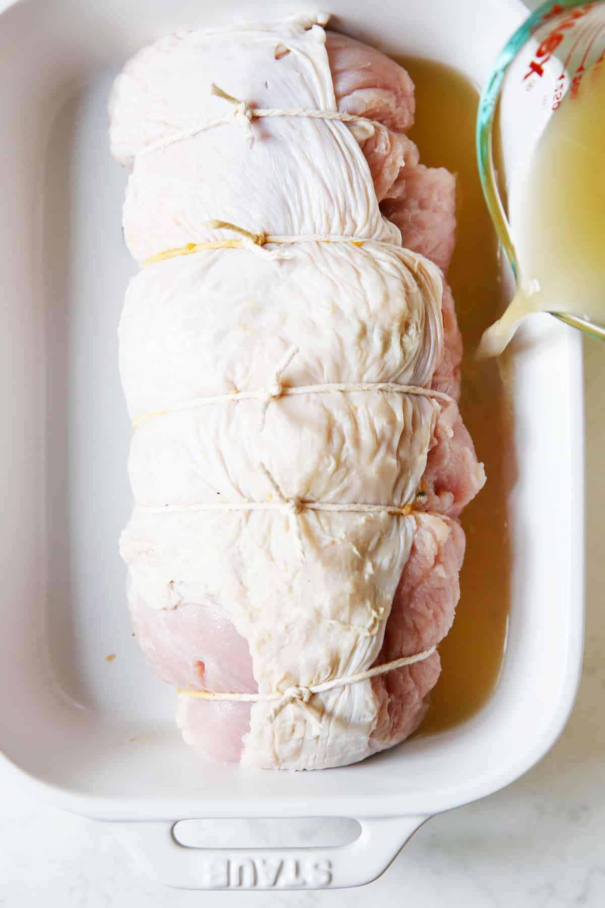 turkey breast stuffed and rolled up in a roasting pan