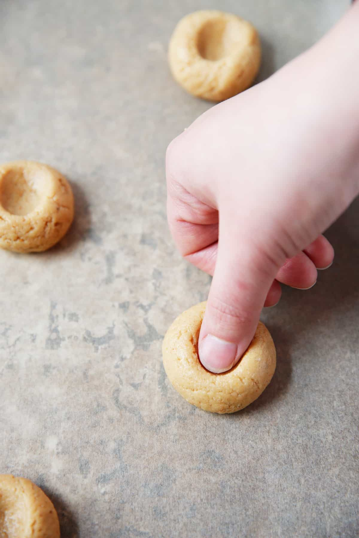Making a thumbprint in cookie dough.