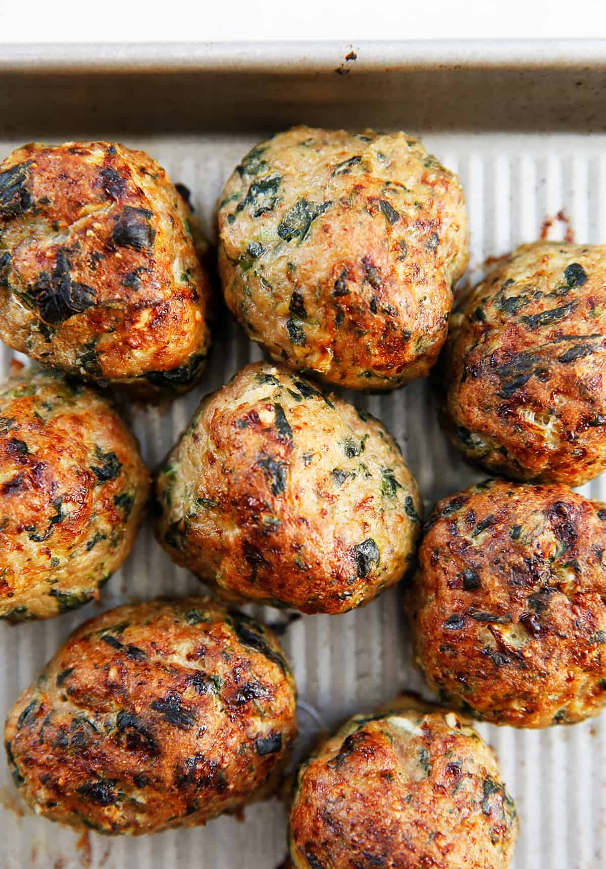 Paleo turkey meatballs with spinach on a sheet pan.