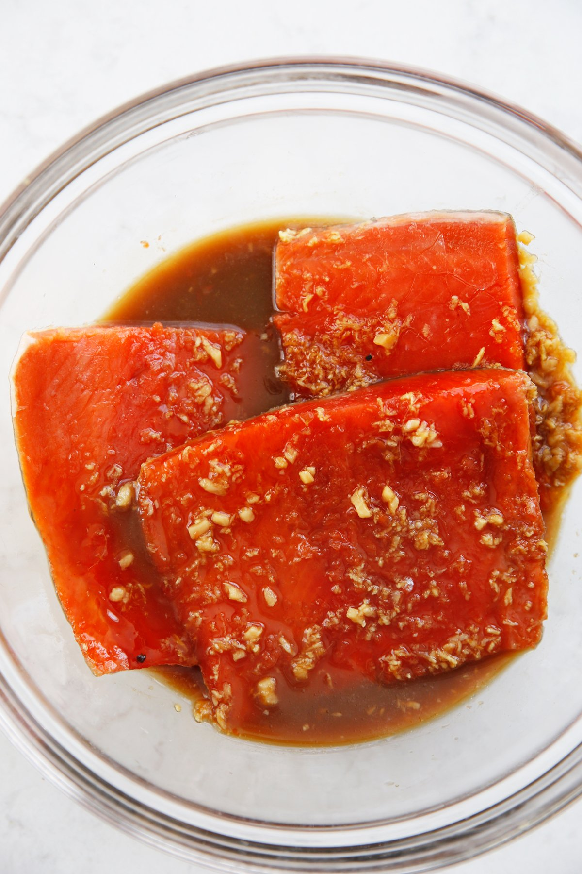 Asian salmon marinating in a bowl.
