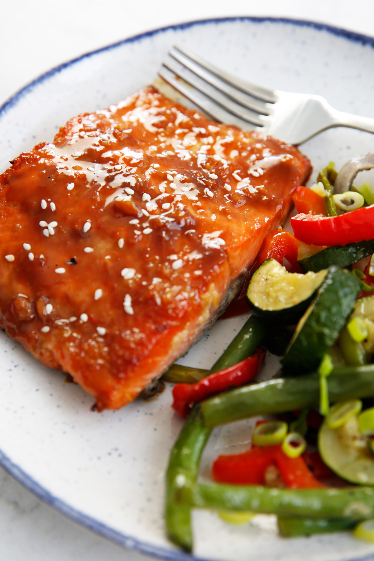A dish of sticky salmon with vegetables.