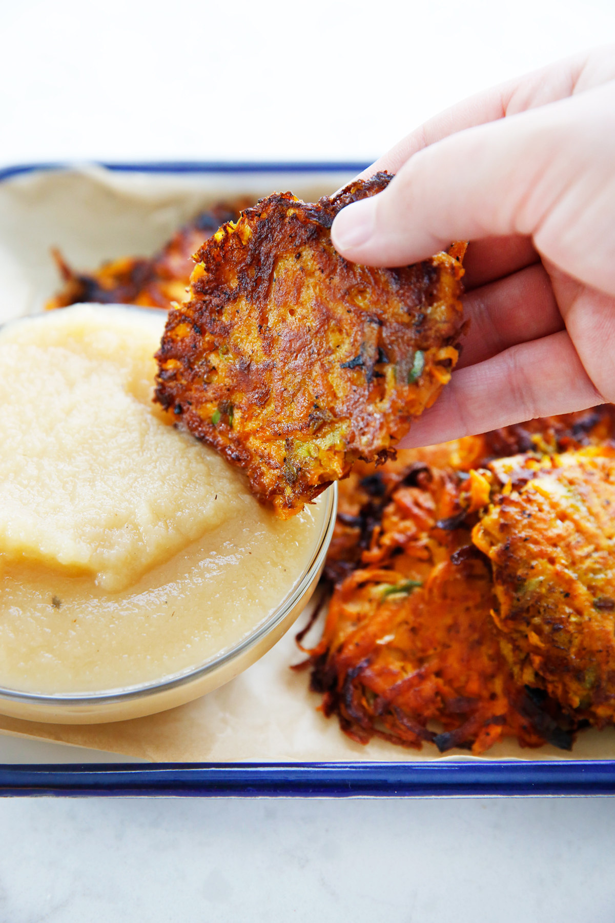 Healthy sweet potato latkes dipped in apple sauce.