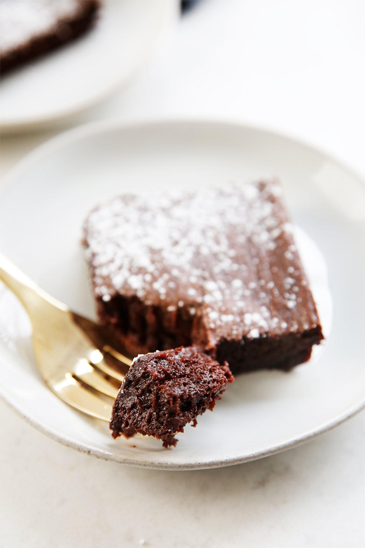 A forkful of fudge-y and dense brownies made with avocado on a plate.