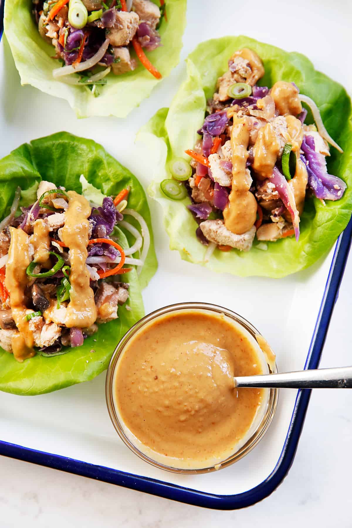 Thai chicken lettuce wraps with peanut sauce on a platter.