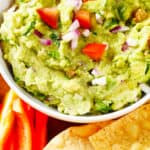Guacamole with cut vegetables and tortilla chips.