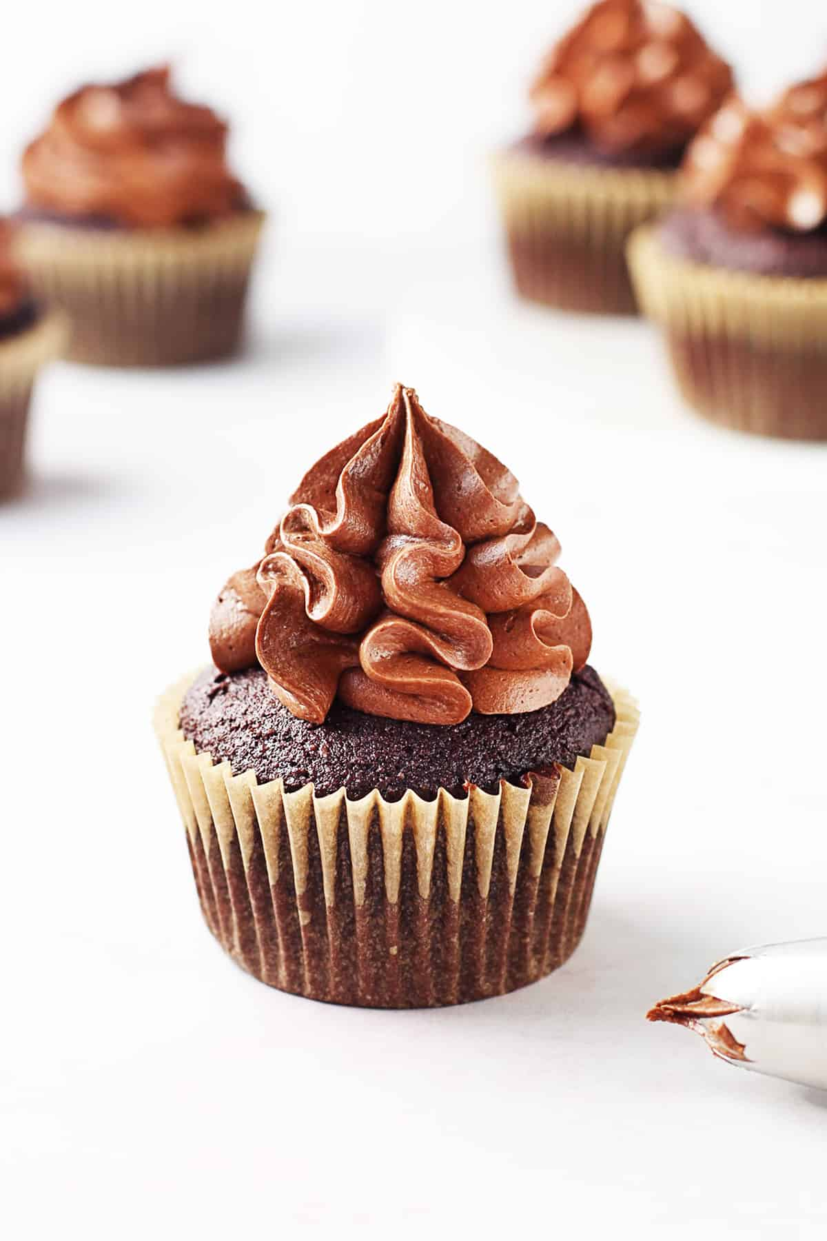 A close up of a gluten free chocolate cupcake with piped frosting on top.